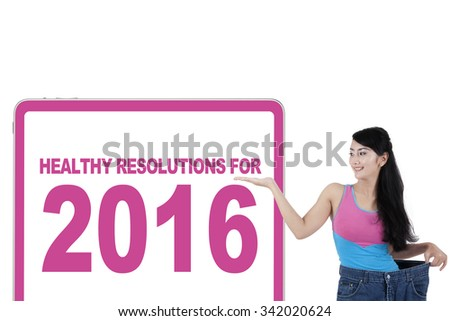 Successful woman lose weight, wearing her old jeans and showing a billboard with healthy resolution for 2016 - stock photo