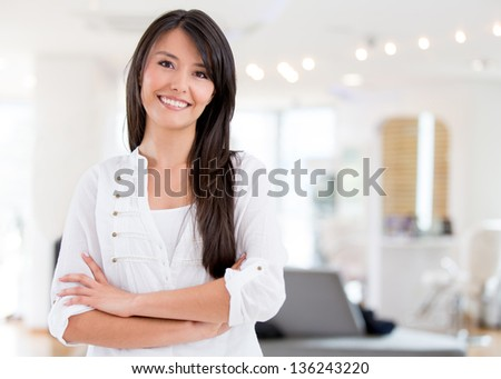 Successful woman owning a hair salon and looking very happy - stock photo