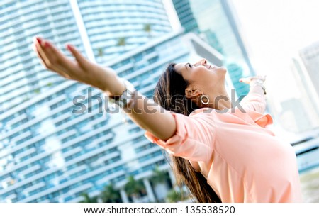 Successful woman with open arms looking very happy - stock photo