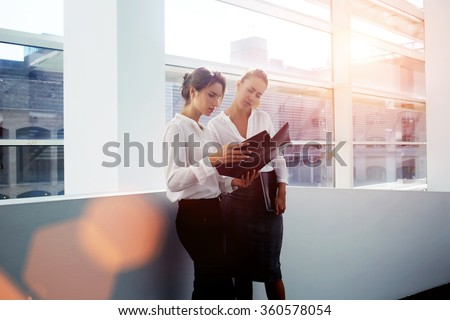 Successful women financiers discussing ideas of own project while standing in modern office interior, young female manager consulting with colleague about presentation while holding folder documents - stock photo