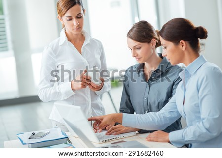 Successful women in business, they are working at office desk, pointing at computer screen and smiling