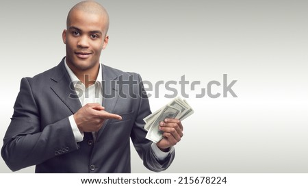 successful young african businessman standing over gray background