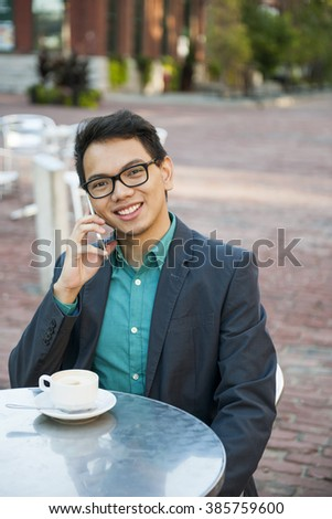 Successful young asian man in business casual attire sitting and smiling in relaxing outdoor cafe with cup of coffee talking on mobile phone - stock photo