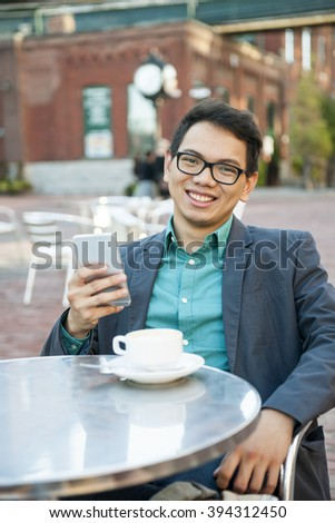 Successful young asian man in business casual attire sitting and smiling in relaxing outdoor cafe with cup of coffee and mobile device - stock photo