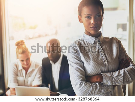 Successful young black business woman standing in front of multi ethnic group of people - stock photo