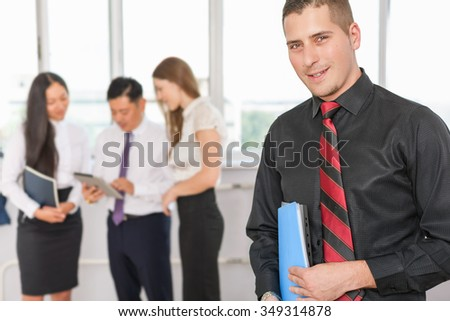 Successful young business man and business team of women and man at background. Image symbolizes a successful corporation or company, achieve success for intelligent and handsome men