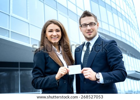 Successful young business people are holding a card, standing in front of his office.