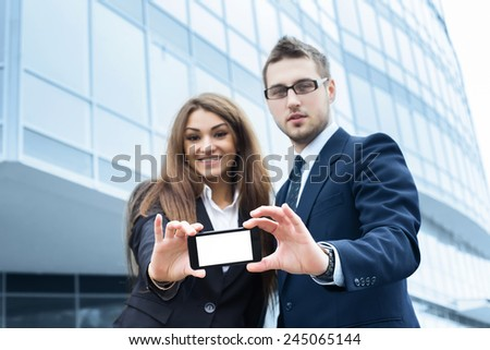Successful young business people are holding a mobile, standing in front of his office. - stock photo