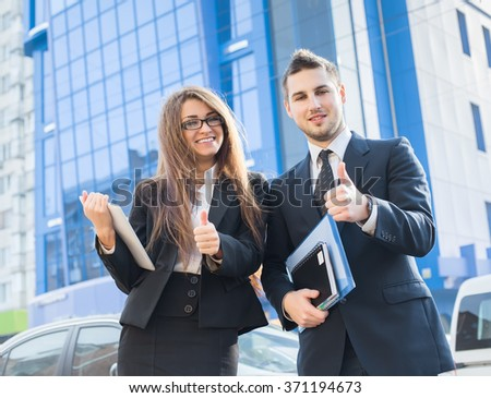 Successful young business people showing thumbs up sign, standing in front of his office.