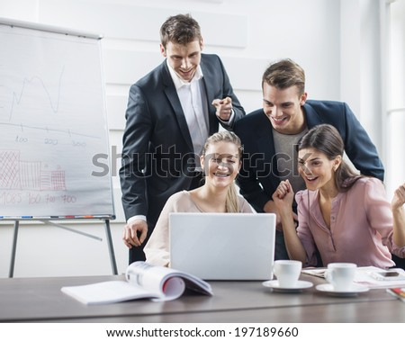 Successful young business people using laptop in meeting