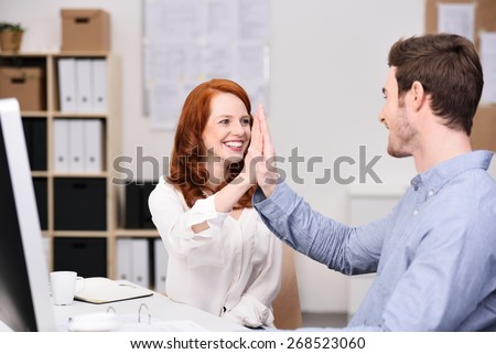 Successful young business team celebrating and giving a high fives as they laugh and smile, man and woman in an office - stock photo