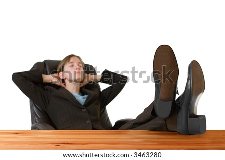Successful, young business woman in a tailored suit resting with feet up on a desk. Image is isolated on a white background. - stock photo