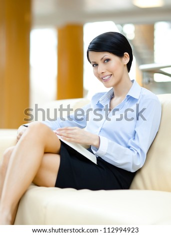 Successful young business woman rests at the sofa reading book at the hall