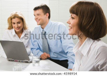 Successful young business woman with charming confident smile on the background of her colleagues