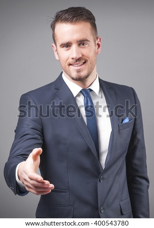 Successful young businessman giving his hand for handshake - stock photo