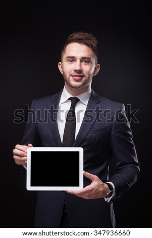 successful young businessman in a stylish business suit on a black background confident holding tablet display forward and smiling. - stock photo