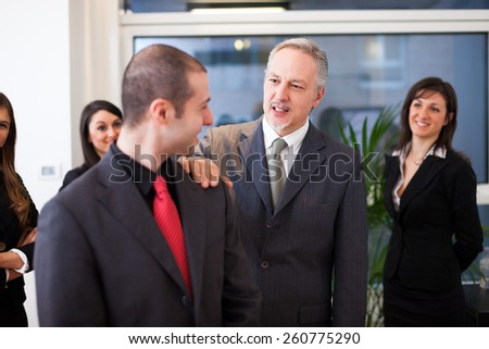 Successful young businessman receiving greetings from his colleagues - stock photo