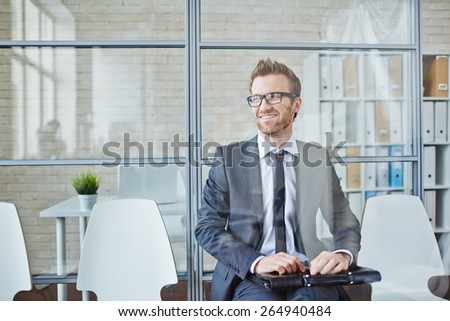 Successful young businessman sitting in office