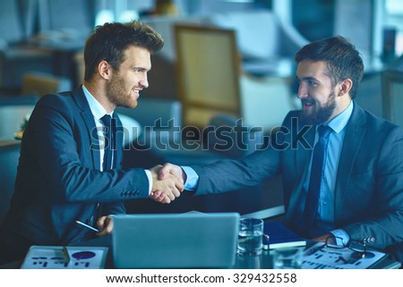 Successful young businessmen handshaking at meeting - stock photo