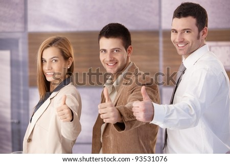 Successful young businessteam smiling happily with thumbs up?