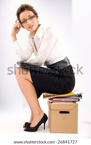 Successful young businesswoman sitting on pile of documents