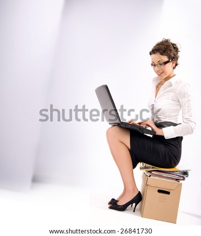 Successful young businesswoman sitting on pile of documents, lots of copy space - stock photo