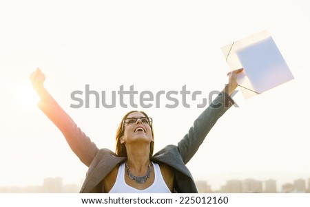 Successful young businesswoman with arms up celebrating business  or job success towards city skyline on sunset or sunrise. Professional happy woman outside. - stock photo
