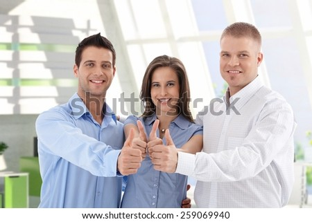Successful young caucasian casual startup business team giving thumbs up at financial center. Smiling, standing, looking at camera. - stock photo