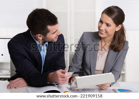 Successful young consultants working as business team in an office analyzing documents. - stock photo