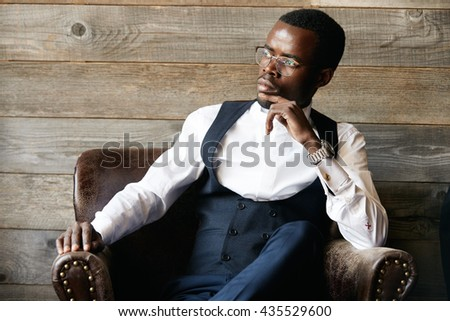 Successful young dark-skinned entrepreneur in formal clothing, sitting in leather armchair against wooden background, thinking and making plans for future, while relaxing after hard day in the office - stock photo