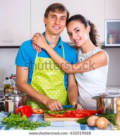 Successful young family couple cooking vegetables in domestic kitchen