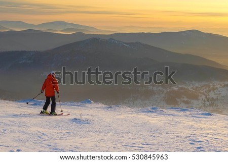 Successful young man skiing in the mountains Sheregesh. Skier resting on mountain top. Caucasian Skier on a background of sky . Skier on a background of a bright sunset.