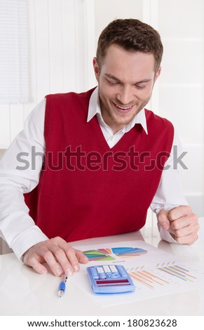 Successful young smiling attractive business man with pocket calculator at desk.