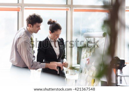 successful young startup business people group brainstorming  planning projects and taking notes to white flip board and checking tablet computer  at modern bright office interior - stock photo