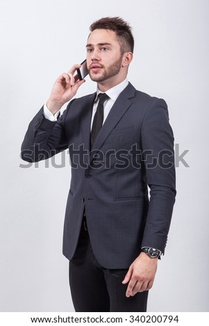 successful young student in a classic stylish suit talking on the phone on a white background gesturing hands. - stock photo
