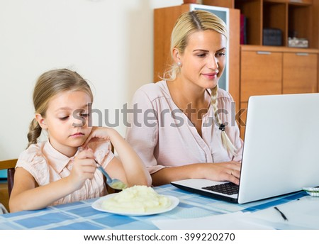 Successful young woman with little daughter working from home using laptop. Focus on woman