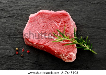Succulent cut of raw lean rump steak waiting to be cooked with a sprig of fresh rosemary for seasoning and whole peppercorns, view from above on a dark kitchen counter - stock photo