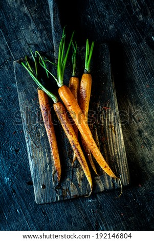 Succulent fried fresh young carrots served whole on an old rustic wooden chopping board for healthy vegetarian fare, overhead view - stock photo