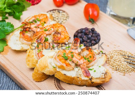 succulent grilled shrimp on toast with cheese and cherry tomatoes on a wooden plate