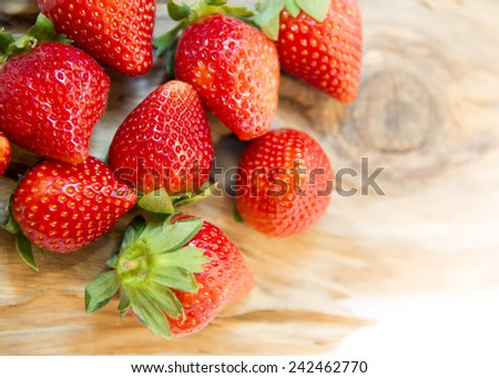 Succulent juicy fresh ripe red strawberries on wooden plate - stock photo