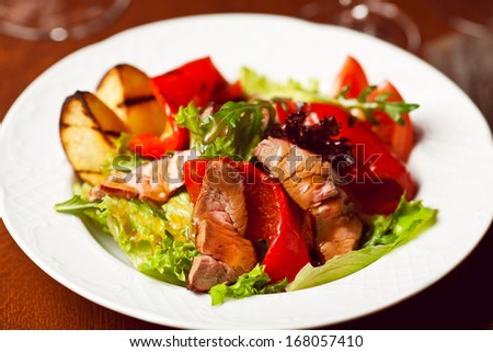 Succulent juicy portion of hot salad with grilled fillet steaks served with tomatoes, ruccola and roast vegetables on white plate. Haute cuisine concept. Indoor shot