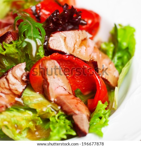 Succulent juicy portion of hot salad with grilled fillet steaks served with tomatoes, ruccola and roast vegetables on white plate. Copy-space.  Close up. Indoor shot - stock photo
