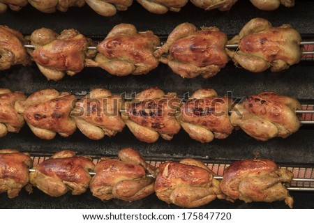 Succulent roasting chickens on a rotisserie at a market - stock photo