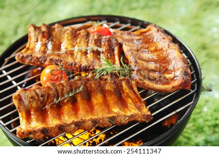 Succulent spicy spare ribs on a barbecue grilling over the hot coals with fresh rosemary and thyme and cherry tomatoes, outdoors on grass