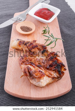 Succulent thick juicy portions of grilled fillet steak served with tomatoes  dip  on an old wooden board - stock photo