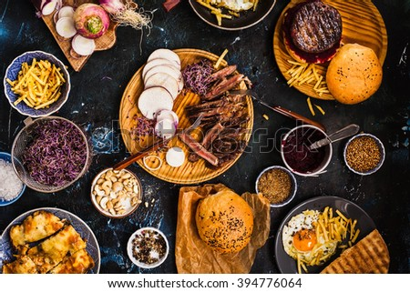 Succulent thick juicy portions of grilled fillet steak served with variety veggies dips , micro greens, fries potatoes, egg, bread buns on a old vintage table  Authentic dinner party. - stock photo