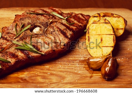 Succulent thick juicy portions of grilled fillet steak with bone served with rosemary and roast vegetables - garlic and potato - on an old wooden board. Vintage style. Close up - stock photo