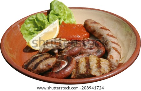 Succulent thick juicy portions of grilled sausages, steak and meat balls served with tomato sauce on an traditional plate - stock photo