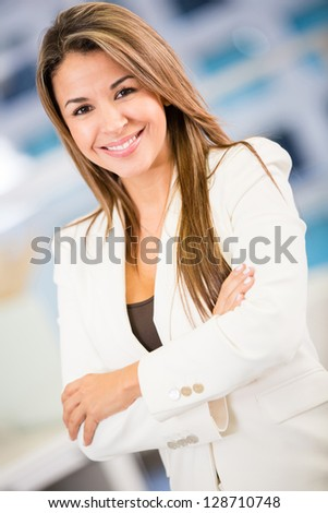 Sucessful business woman looking happy at the office - stock photo
