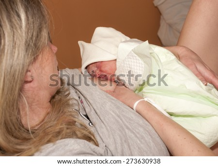 suckling of a newborn baby after delivery - stock photo